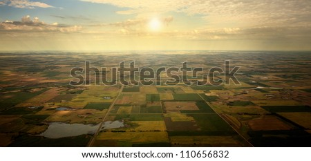 Sunrise on Horizon - illustrated sunrise over an aerial view of South Dakota farm land - stock photo