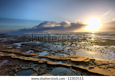 Sunrise on rocky beach - against sun. Shot in Sodwana Bay Nature Reserve, KwaZulu-Natal province, Southern Mozambique area, South Africa. - stock photo