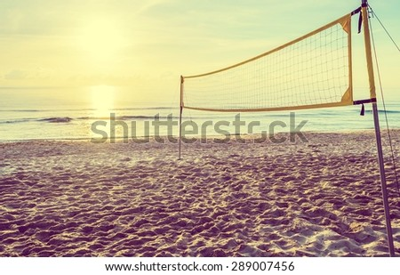 sunrise on the beach and volleyball net with vintage tone style - stock photo