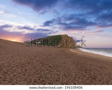 Sunrise on the beach underneath the cliffs and headland at West Bay in Dorset. This was used as the location for the Broadchurch TV series - stock photo
