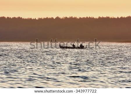 Sunrise on the lake with boat fishermen - stock photo