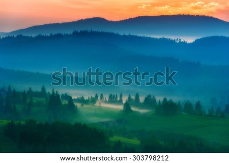 sunrise on the mountain slopes of the middle road bridge fog tree - stock photo