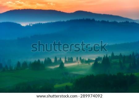 sunrise on the mountain slopes of the middle road bridge fog tree, soft focus - stock photo