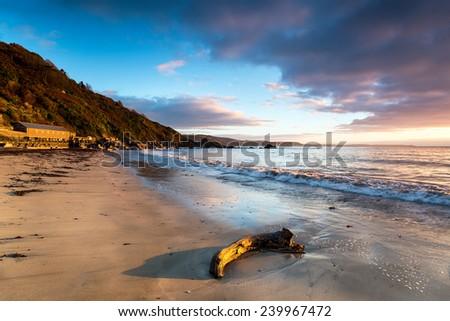 Sunrise ont the sandy beach at Looe in Cornwall - stock photo