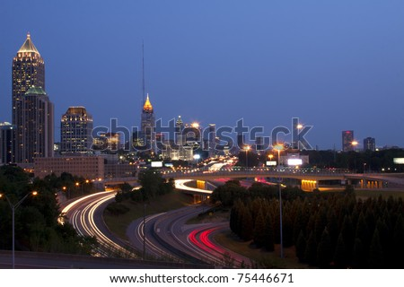 Sunrise or sunset downtown Atlanta skyline showing trails of car headlights and tail lights - stock photo