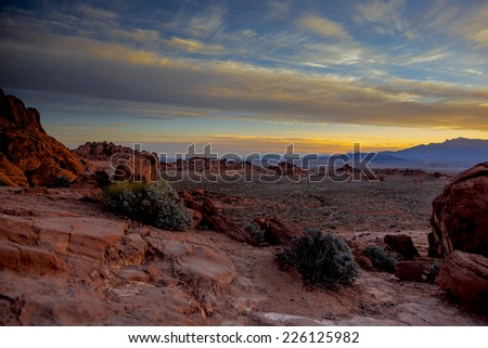 Sunrise over a desert landscape with red sandstone and sparse vegetation. - stock photo
