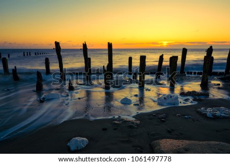 Sunrise over beach at Spurn Point Nature Reserve as tide washes around old wooden sea defenses, East Yorkshire, UK.