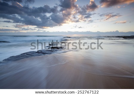 sunrise over beach in calm day - stock photo