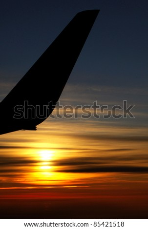 Sunrise over clouds with contour of airplane wing - stock photo