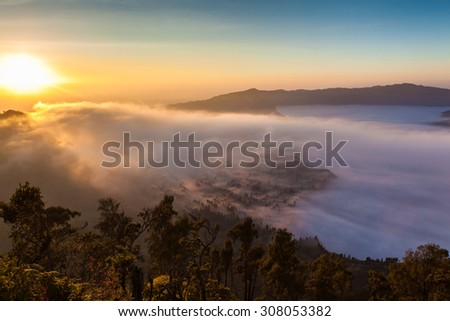 Sunrise over foggy mountains and tropical forest - stock photo