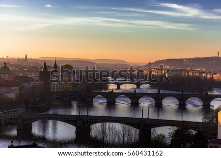 Sunrise over historical Prague bridges with Vltava river Bohemia Czech Republic Europe. Historical buildings / landmarks banks and illuminated panoramic scenery with mirror reflection in river.
