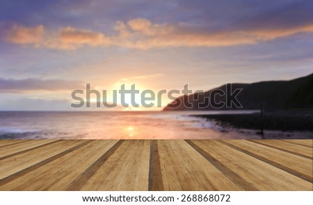 sunrise over incoming tide with rocky foreground and cliffs with wooden planks floor - stock photo