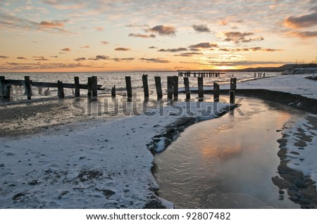 sunrise over lake with frozen stream in foreground - stock photo