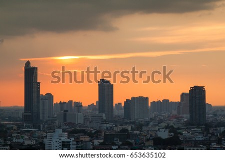 Sunrise over modern office buildings in business district center of Bangkok. Skyline view of cityscape with sunlight and flare in warm light color tone. Construction business concept.