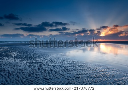 sunrise over North sea coast at low tide, Schiermonnikoog, Netherlands - stock photo