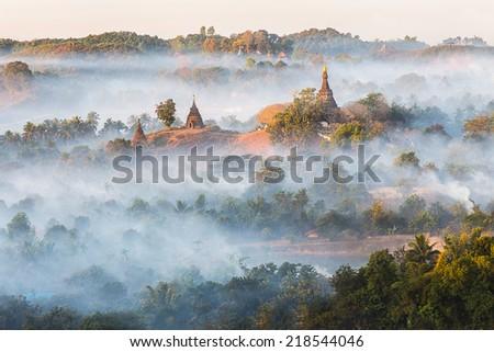 Sunrise over pagodas of  Mrauk U in the mist at the northern Rakhine State, Myanmar   - stock photo