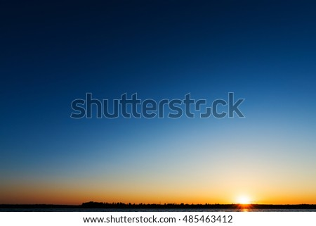 sunrise over river in deep blue sky