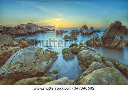 Sunrise over sea Binh Thuan reef with rocky path rising sun to radiate glamor beautiful welcome new day. - stock photo