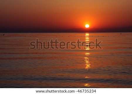 Sunrise over sea. The sun appears from behind the mountains on the horizon. - stock photo