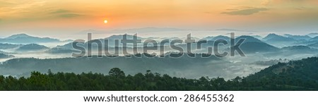 Sunrise over the panoramic mountains of Da Lat  with his sun rise on the hill waxing pine soon covered with clouds and fog do to honor the beauty highland Da Lat - stock photo