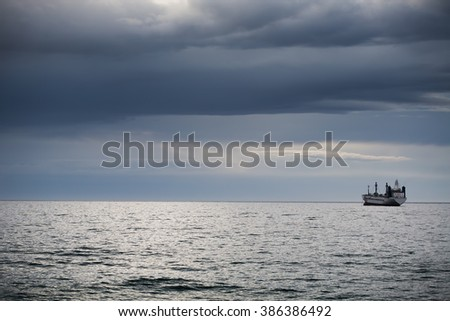 Sunrise over the sea and sailing cargo ship