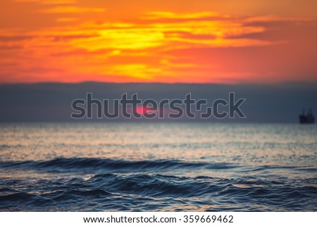 Sunrise over the sea landscape. Cargo ship sailing in the water.