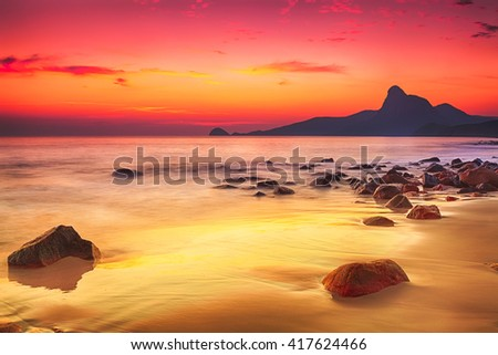 Sunrise over the sea. Stone on the foreground - stock photo