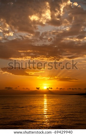 Sunrise over the sea with golden clouds - stock photo