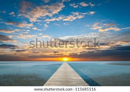 Sunrise over the sea with pier on the foreground - stock photo