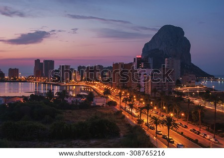 Sunrise over the summer mediterranean resort Calpe in Costa Blanca, Spain. Aerial view of buildings - hotels and apartments, famous mountain Penon de Ifach and lake. Colorful sky, illuminated road - stock photo