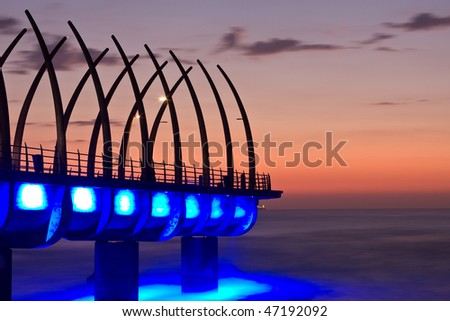 Sunrise over Umlanga Pier with blue lights reflecting in the ocean - stock photo