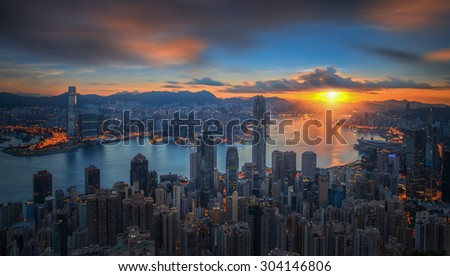 Sunrise over Victoria Harbor as viewed atop Victoria Peak with Hong kong and Kowloon below - stock photo