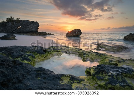 Sunrise reflections into a  lava formed natural pool in Bermuda - stock photo