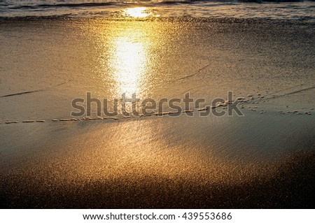 sunrise scenery. Calm water on beach and sand
