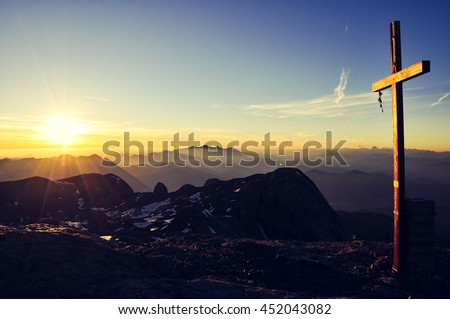 Sunrise seen from the summit of Hochkoenig mountain (Austria) at 2941m above sea level in the Berchtesgaden alps. Summit cross lit by rising sun. Dachstein group in background. Image cross processed. - stock photo