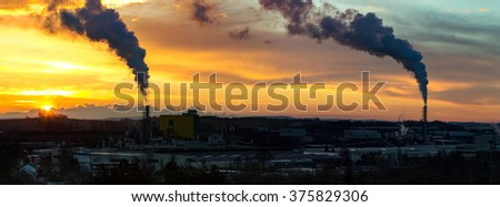Sunrise silhouette of city landscape with smoking factory, ecology pollution concept - stock photo