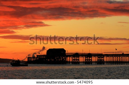 Sunrise Silhouette of Mumbles pier and boat house - Swansea Wales UK - stock photo