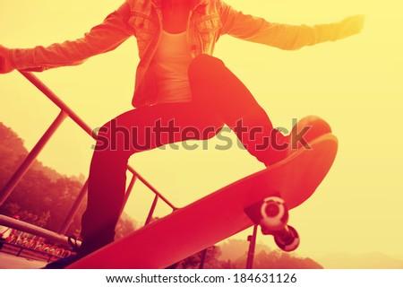 sunrise skateboarding woman - stock photo