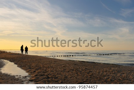 Sunrise walk of couple at beach - stock photo