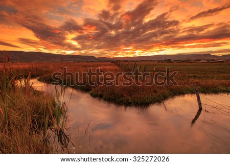 Sunrise with a stream in a rural valley, Utah, USA.