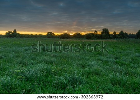 Sunrise with cloudy sky over beautiful summer meadow. Nature landscape. - stock photo