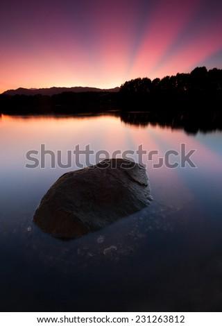 Sunrise with reflection of rays - stock photo