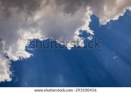Suns rays beaming from behind clouds - stock photo