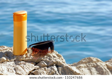 Sunscreen and sunglasses on a rock by the water.