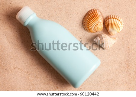 sunscreen in sand - stock photo