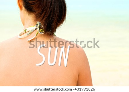 Sunscreen lotion over woman skin, Sun protection. SUN word. Back view. Close up. - stock photo