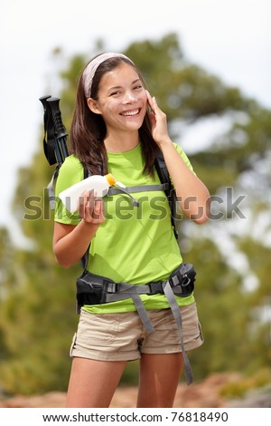 Sunscreen lotion woman. Woman hiking putting sun block lotion outside during summer hike vacation. Asian Caucasian female model. - stock photo