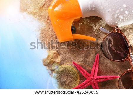Sunscreen spray and sunglasses on sand in blue glass table with sun shine. Horizontal composition. Top view - stock photo