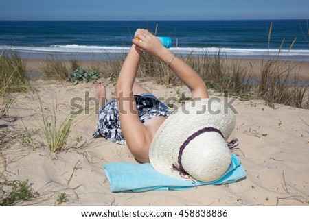 Sunscreen woman showing suntan lotion bottle applying solar cream to arms. Beautiful smiling happy woman with suntan cream