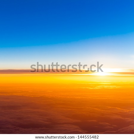 sunset above clouds. View of sunset  from airplane window - stock photo